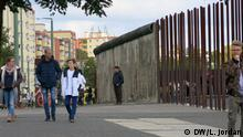 Passers-by walk along the course of the Berlin Wall, which is marked by strips of the former wall and metal poles