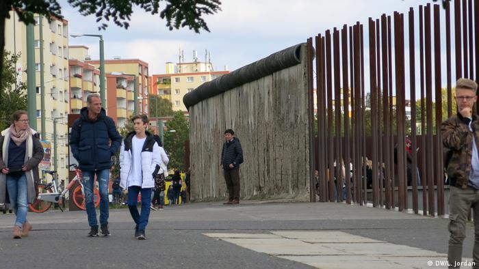 Menschen laufen in der Bernauer Straße in Berlin an Mauerresten und Metallstäben vorbei