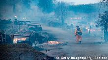 A firefighter walks through a burned property after the Kincade fire tore through Healdsburg, California on October 27, 2019. - Powerful winds were fanning wildfires in northern California in potentially historic fire conditions, authorities said October 27, as tens of thousands of people were ordered to evacuate and sweeping power cuts began in the US state. (Photo by Josh Edelson / AFP) (Photo by JOSH EDELSON/AFP via Getty Images)