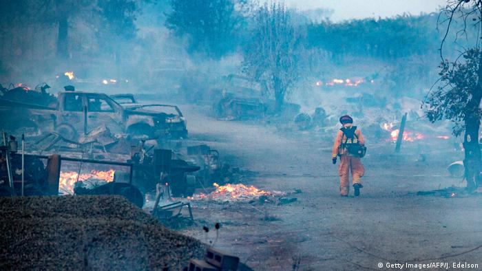 A fireman walks down a street littered with burned out cars and homes, where small fires are still burning