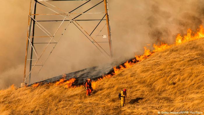 Feuerwehrleute kämpfen am Fuße einer PG&E-Stromtrasse gegen die Flammen