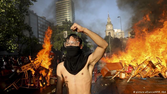 Manifestante semi-mascarado em frente a uma barricada incendiada numa via em Santiago, no Chile