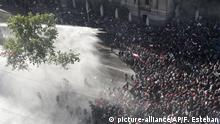 Police sprays water on anti-government demonstrators in Santiago, Chile, Monday, Oct. 28, 2019. President Sebastian Pinera announced changes in his cabinet in hopes of bringing peace back to the streets after days of protests that originally started over a hike in subway fares and have grown into a wider range of demands such as better pay, pensions, schools, housing and medical care.(AP Photo/Esteban Felix) |