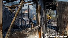 Firefighters battle the Getty Fire in houses on fire in Brentwood, California on October 28, 2019. - A wildfire broke out early Monday near the renowned Getty Center in Los Angeles, forcing widespread evacuations as the flames destroyed several homes in hillside communities. The so-called Getty Fire broke out overnight near a major freeway and quickly spread south and west, scorching 500 acres (202 hectares) and sending people fleeing in the dark. (Photo by Apu Gomes / AFP) / The erroneous mention[s] appearing in the metadata of this photo by Apu Gomes has been modified in AFP systems in the following manner: [Getty Fire] instead of (Tick Fire]. Please immediately remove the erroneous mention[s] from all your online services and delete it (them) from your servers. If you have been authorized by AFP to distribute it (them) to third parties, please ensure that the same actions are carried out by them. Failure to promptly comply with these instructions will entail liability on your part for any continued or post notification usage. Therefore we thank you very much for all your attention and prompt action. We are sorry for the inconvenience this notification may cause and remain at your disposal for any further information you may require. (Photo by APU GOMES/AFP via Getty Images)