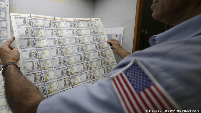 Работник типографии держит свежеотпечатанные новые 100-долларовые купюры