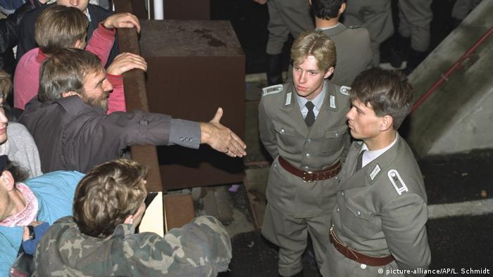 10 ноември 1989: източногермански гранични полицаи отказват да се ръкуват с ликуващи берлинчани, подаващи им ръка през Берлинската стена