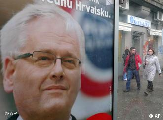 A couple walk near the election poster of Croatian presidential candidate Ivo Josipovic, of the Social Democrats in Zagreb, Croatia,