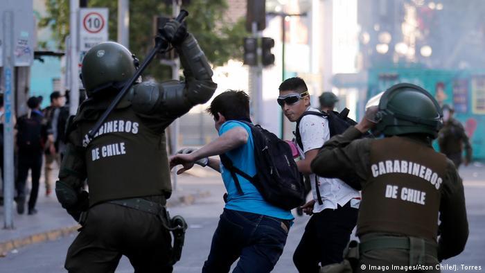 Foto de carabineros siguiendo a manifestantes en Chile