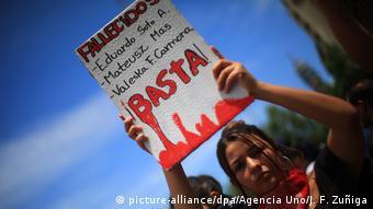 Foto de manifestante que lleva un rótulo con nombres de fallecidos en Chile