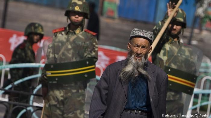 A Uighur man and security forces in Urumqi, Xinjiang, China
