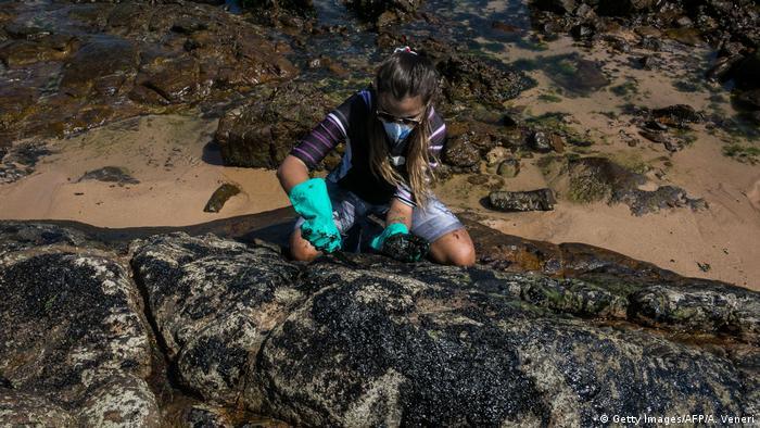 Voluntária limpa rocha na praia baiana de Pedra do Sal em meados de outubro