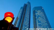ARCHIV - Eine Verkehrsampel steht am 08.01.2014 nahe der Zentrale der Deutschen Bank in Frankfurt am Main (Hessen) auf Rot. Die Deutsche Bank ist im Umbruch und hat 2016 zum Übergangsjahr erklärt. Alles andere als erneut rote Zahlen wären eine Überraschung. (zu dpa Deutsche Bank bilanziert Übergangsjahr 2016 - Rote Zahlen erwartet vom 01.02.2017) +++(c) dpa - Bildfunk+++ | Verwendung weltweit