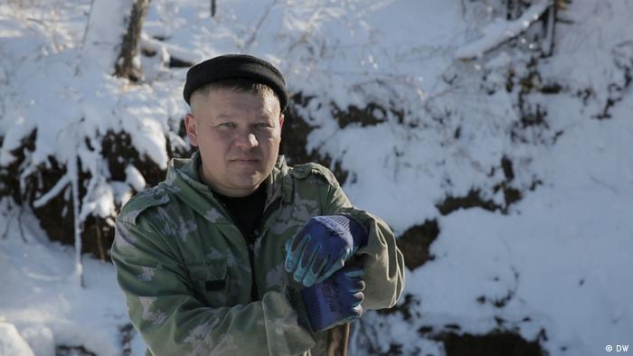 Vitaly Kvasha stands outside in the snow leaning on a shovel (DW)