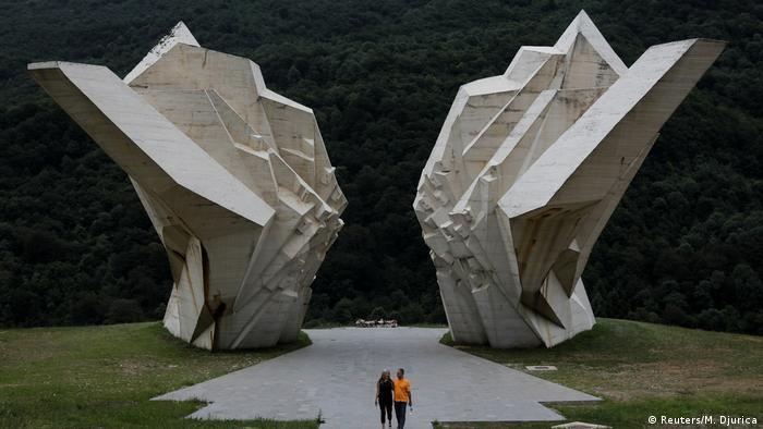 two large jagged slabs of concrete facing each other, two people in the foreground,Sutjeska war memorial (Reuters/M. Djurica)