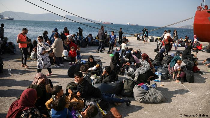 Refugees and migrants wait to be transferred to camps