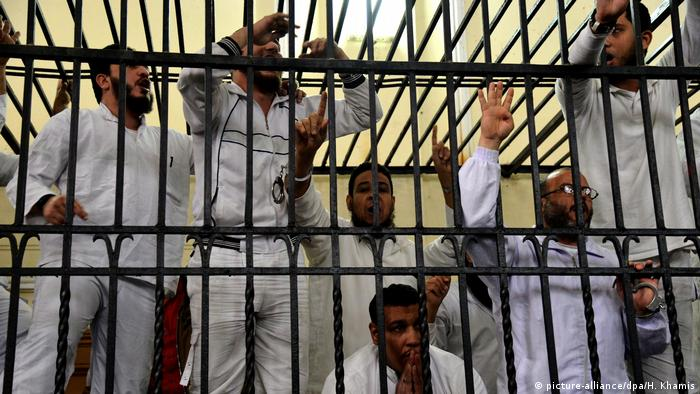 Men shout behind bars during a trial in Alexandria, Egypt