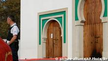 A police officer stands next to the entrance a mosque after an incident in Bayonne, southwestern France