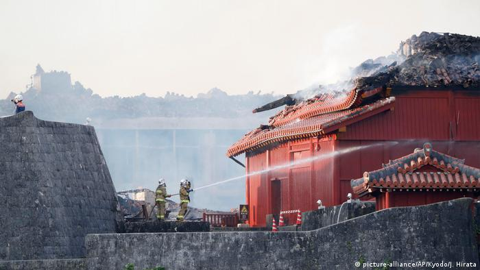Firefighters aim their hoses at Shuri Castle