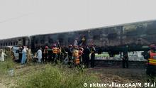 RAHIMYAR KHAN, PAKISTAN - OCTOBER 31: Pakistani rescuers shift a victim from a train as fire erupted in it in a gas cylinder blast at Chani Goth area in Rahimyar District in southern Punjab province on October 31, 2019. Punjab provincial health minister Dr. Yasmin Rashid said more than 62 people were killed and over 40 injured in the when a gas cylinder stove burst into flames at Tezgaam passenger train in Pakistan southern Punjab province on Thursday. MUHAMMAD BILAL / Anadolu Agency   Keine Weitergabe an Wiederverkäufer.