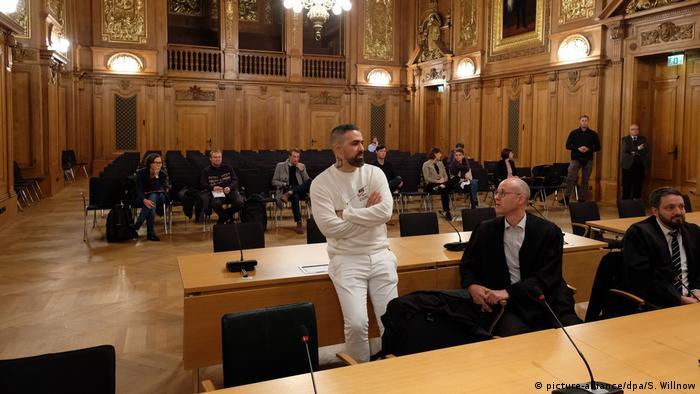 Bushido in weißer Hose und weißem Pulli zieht mit verschränkten Armen auf einem Tisch eines Gerichtssaals (Foto: picture-alliance/dpa/S. Willnow).