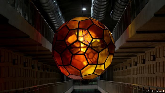 A glass lightsphere by Gabriel hangs in the Har Hamenuchot catacombs and glows red and orange