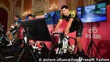 Drei Radsportler auf Rollentrainern mit Bildschirmen vor sich, die mit einem Radsportvideospiel den Giro d'Italia fahren (picture-alliance/ZumaPress/M. Paolone)