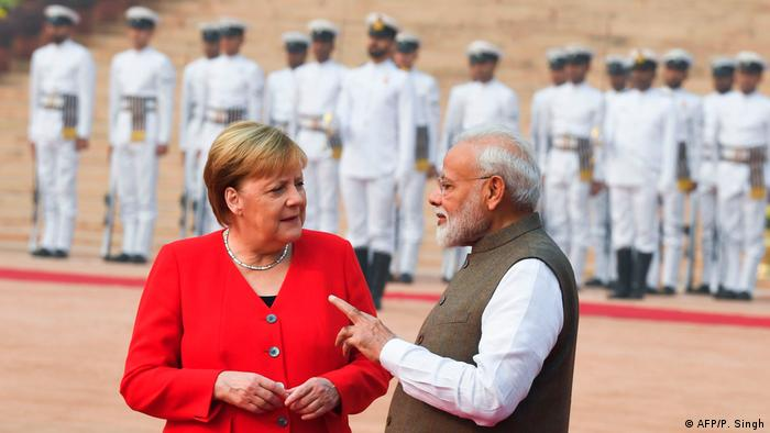 Merkel and Modi talk to each other. Merkel is wearing red and Modi is wearing a brown waistcoat and white shirt. Presidential guards stand in the background