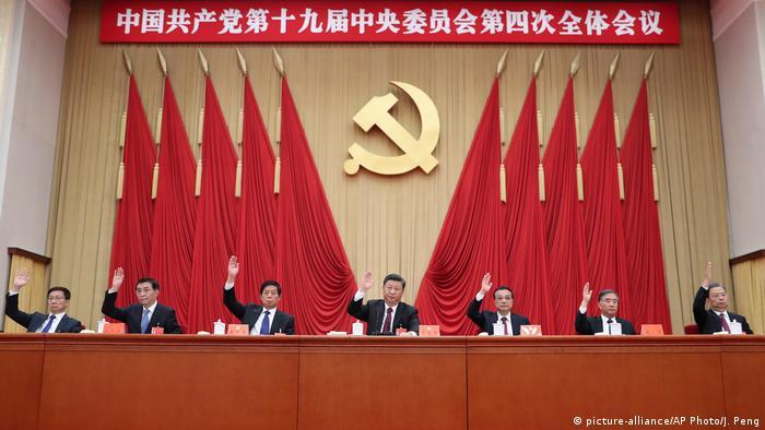 Plenarsitzung des Zentralkommitees In China: Männer, in der Mitte Xi Jinping, sitzen vor roten Flaggen und dem Symbol Hammer und Sichel. Sie haben eine Hand zur Abstimmung erhoben