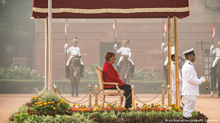 Angela Merkel in profile, wearing a red jacket and sitting on a golden throne-like chair under a maroon shelter. Indian guards in white sit on horses in the background