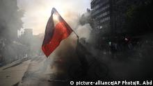 A demonstrator waves a Chilean national flag poked with holes during clashes between anti-government protesters and police, in Santiago, Chile, Thursday, Oct. 31, 2019. Thousands of young Chileans marched Thursday to demand improved social services as government and opposition leaders debate the response to nearly two weeks of protests that have paralyzed much of the capital and forced the cancellation of two major international summits. (AP Photo/Rodrigo Abd) |