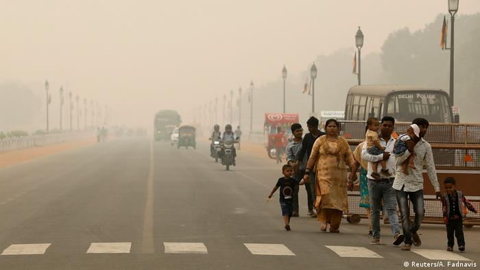 People walk on the Rajpath on a smoggy day in New Delhi