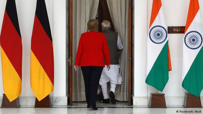 Merkel and Modi walking past German and Indian flags into a room for talks
