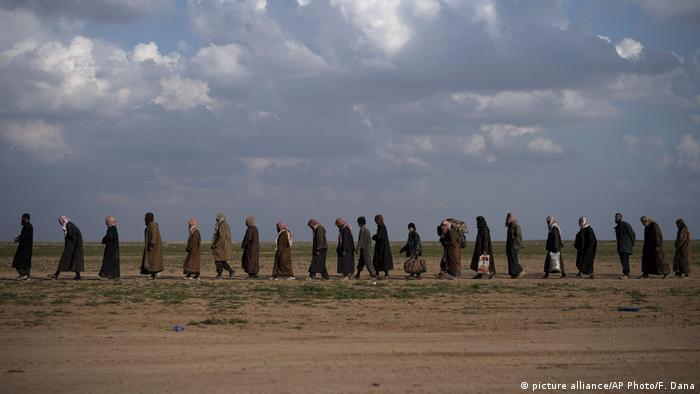 Homens de vestes árabes andam em fila indiana em estrada de terra