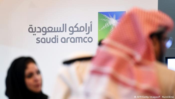 Saudi and Foreign investors stand in front of the logo of Saudi state oil giant Aramco