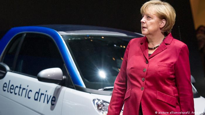 Angela Merkel standing in front of an electric car