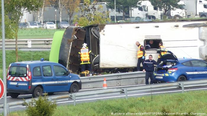 Emergency services assess a bus lying on its side