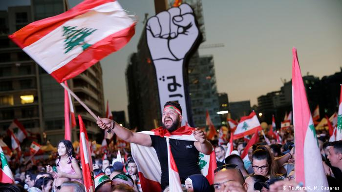 A protester waves a Lebanese flag in a crowd in Beirut (Reuters/A. M. Casares)