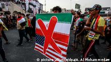 03.11.2019 03.11.2019, Irak, Bagdad: Ein Demonstrant hält ein Banner mit der Flagge des Iran und der USA, über denen ein rotes Kreuz prangt. In Bagdad blockierten Demonstranten am Sonntag mehrere Hauptstraßen, was nach Angaben von Augenzeugen zu massiven Staus führte. Foto: Ameer Al Mohammedaw/dpa +++ dpa-Bildfunk +++