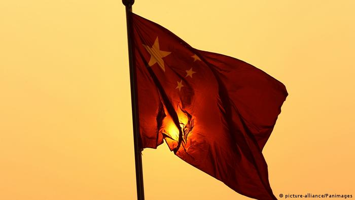 The sun is hidden behind a Chinese flag
