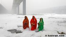 Hindu women worship the Sun god in the polluted waters of the river Yamuna during the Hindu religious festival of Chatth Puja in New Delhi, India, November 3, 2019. REUTERS/Adnan Abidi