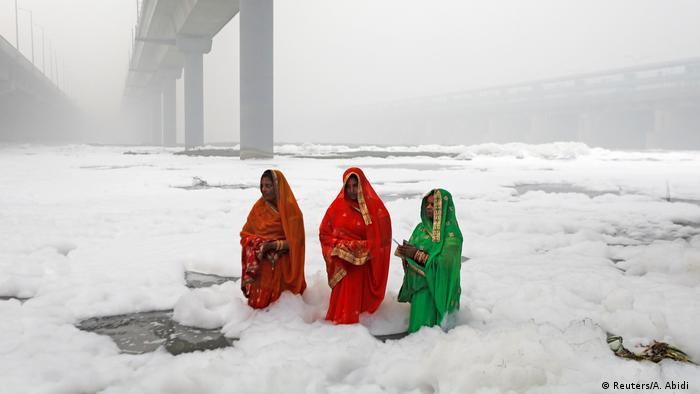 Za hinduistički praznik Chatth Puja obukle su svoje najljepše haljine. One tako žele da odaju počast svom Bogu sunca. No, ne izgleda baš kao da su ga umilostivile. Na ritualnom kupanju u rijeci Jamuna ove žene nisu uopšte blizu nebesima, jer to gdje stoje nisu oblaci, već otrovna pjena, uzrokovana otpadnim i kontaminiranim vodama.