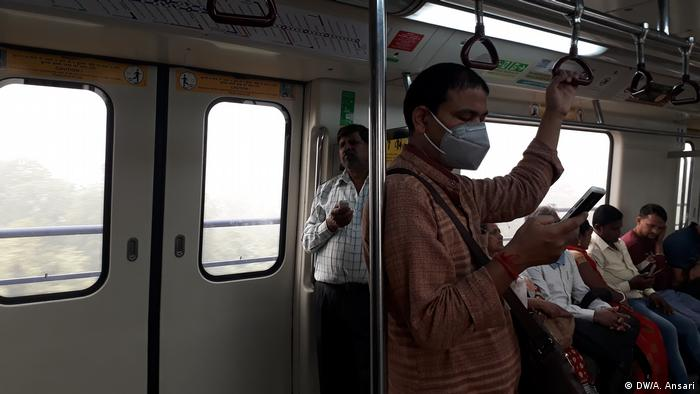A man wearing a face mask on public transport looks at his phone
