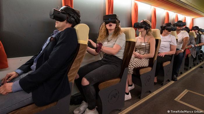 People sitting on replica bus with virtual reality glasses on a TimeRide tour of the former East Berlin