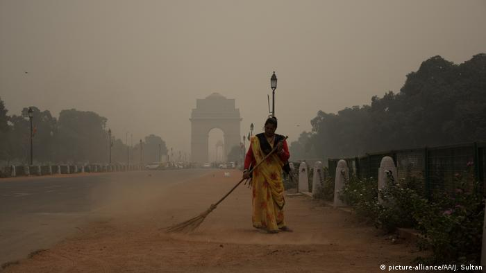 A woman sweeps the side of the road leading to India Gate