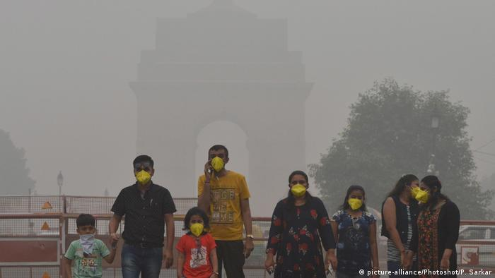 People wearing face masks stand in front of the India Gate