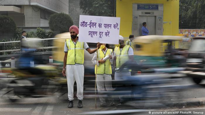 Voluntarios piden obedecer la regla de circulación de matrículas pares e impares. (picture-alliance/AP Photo/M. Swarup)