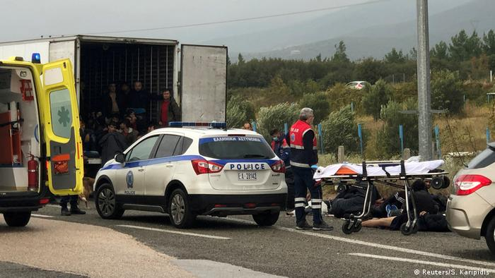 Migrants are seen inside a refrigerated truck as others lie on the road, during a police check on a highway near Xanthi in Greece.