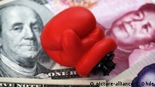 Boxhandschuh auf Dollarnoten und chinesischen Renminbi