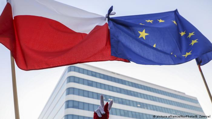 A polish flag and a European Union flag tied together at a demonstration
