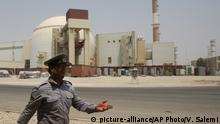 FILE - In this Aug. 21, 2010 file photo, an Iranian security official directs media at the Bushehr nuclear power plant, with the reactor building seen in the background, just outside the southern city of Bushehr, Iran. Iran's nuclear deal with world powers faces its biggest diplomatic challenge yet as President Donald Trump appears poised to withdraw the U.S. from the accord. (AP Photo/Vahid Salemi, File) |